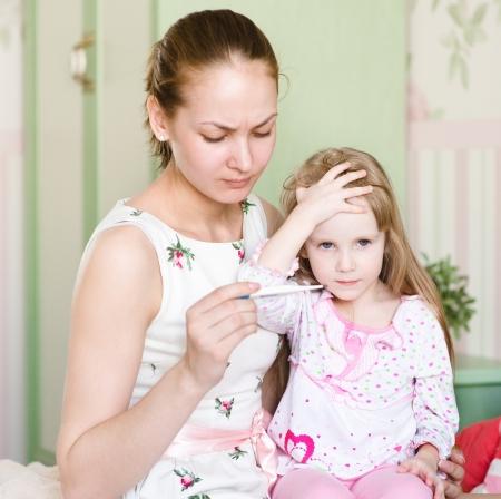 sick kid: mother checks temperature at the sick child Stock Photo