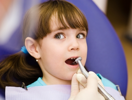 little girl  with open mouth during drilling treatment at the dentist photo