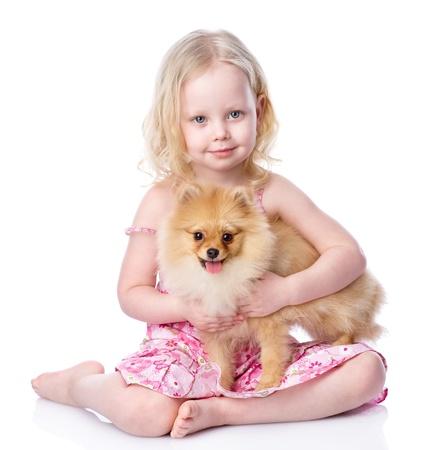 personas abrazadas: ni�a y el perrito mirando a c�mara aislada sobre fondo blanco Foto de archivo
