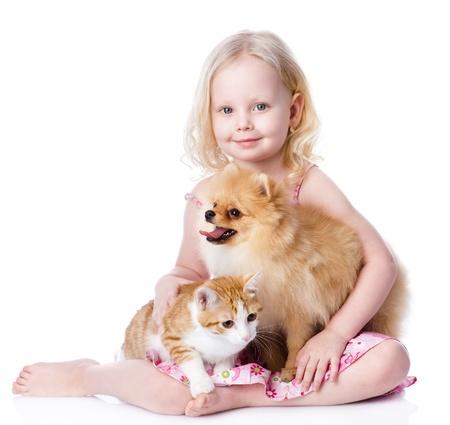 přátelský: dívka si hraje s domácími mazlíčky - pes a kočka odvrátila izolovaných na bílém pozadí