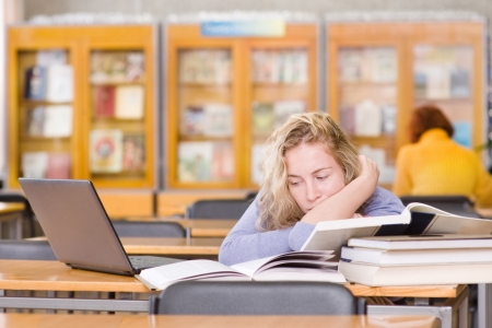 sad student with laptop working in library photo