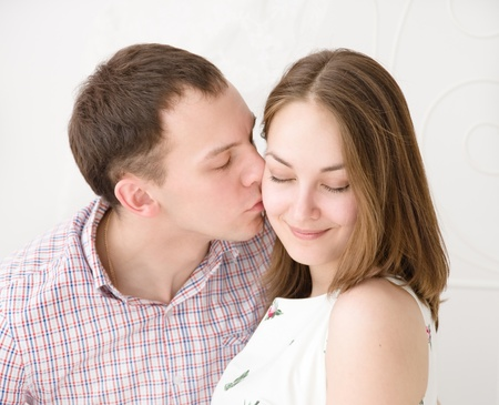 kissing lips: Careful man kissing his smiling girlfriend