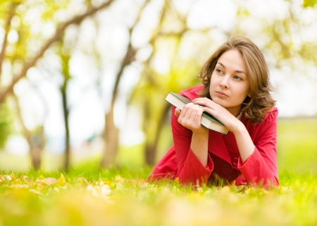 book jacket: Young beautiful woman lays on a grass with the book Stock Photo