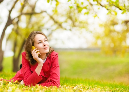 call of nature: young woman talking on cell phone in the autumn park