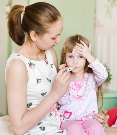 caucasian fever: Sick kid with high fever and mother taking temperature