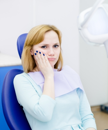 dental chair: woman at the dentist complains of toothache  Looking at camera  Stock Photo