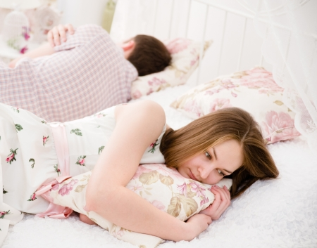 angry woman: Portrait of an upset young woman lying separately from husband on the bed