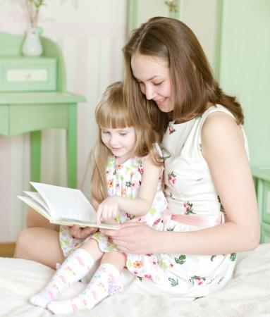 mujer hijos: madre con la hija lee el libro