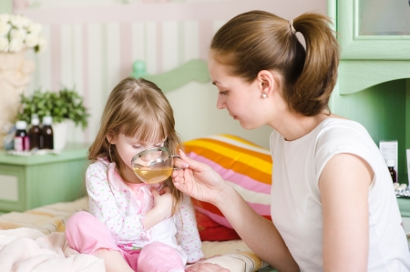 gives: mother gives to drink to the sick child Stock Photo