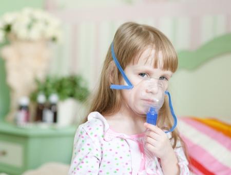 asma: niña con una máscara para inhalaciones