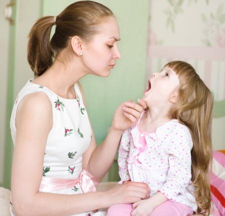 boca abierta: joven madre examinando la garganta ni�a s Foto de archivo