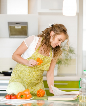 pregnant mother preparing food in kitchen and reading cooking recipe photo