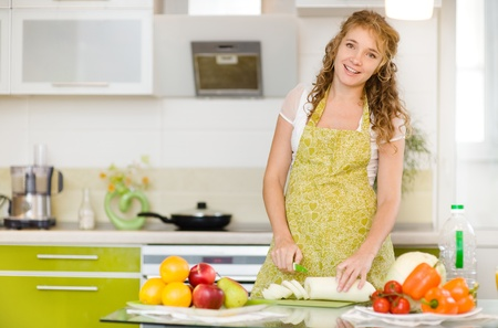 smiling pregnant woman with knife on kitchen photo
