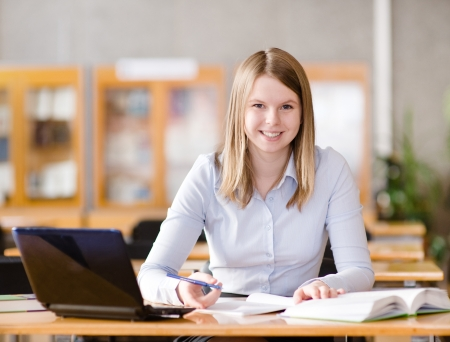tutorials: female student with laptop working in library  looking at camera Stock Photo