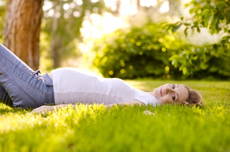 Beautiful pregnant woman lying on the grass in sunny day photo