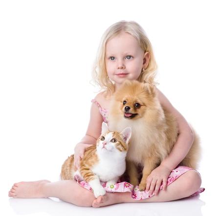 perrito: niña jugando con los animales domésticos - perros y gatos mirando a otro lado aislado sobre fondo blanco Foto de archivo