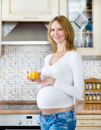 girl belly: Pregnant woman drink juice in the house kitchen Stock Photo