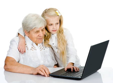 young girl teaching and showing new computer technology to her grandmother  isolated on white background photo