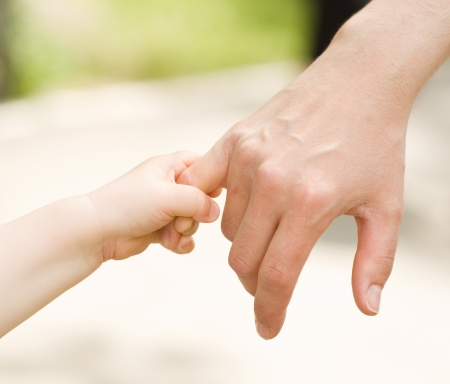 fond of children: father s hand lead his child son Stock Photo