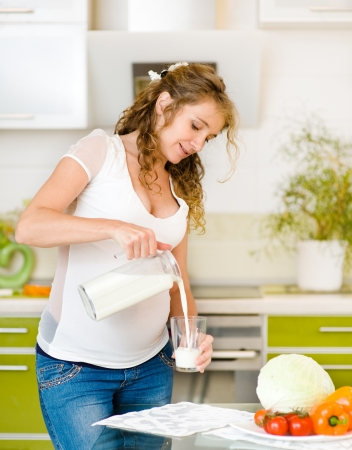 Beautiful pregnant mother pour out milk into glass on the house kitchen photo
