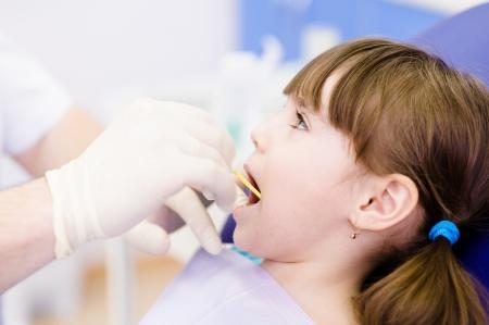 歯科歯科医が小さな女の子に与えられて調べること
