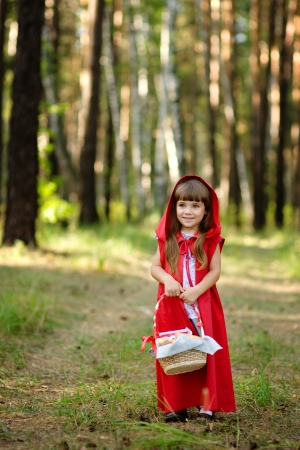 little red riding hood: girl in the wood with a basket looking at camera  the fairy tale   Red Riding Hood