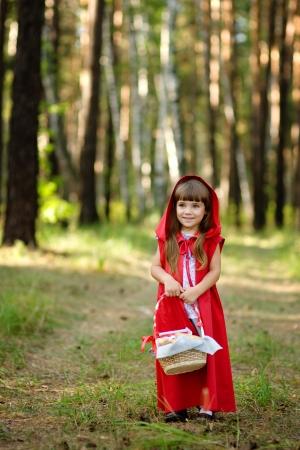 caperucita roja: niña en el bosque con una cesta mirando a la cámara del cuento de hadas Caperucita Roja