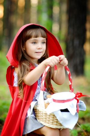 girl sits on hemp with a basket looking away the fairy tale   Red Riding Hood
