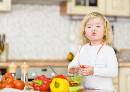 Kid eating healthy vegetables meal in the kitchen photo