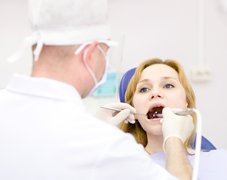 young woman with open mouth during drilling treatment at the dentist photo
