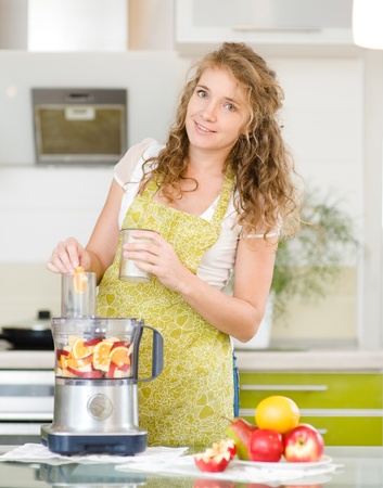 Portrait of a smiling pregnant woman cooking in her kitchen  looking at camera
