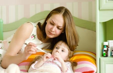 ragazza malata: Bambino ammalato con febbre alta che a letto e la madre di misurare la temperatura