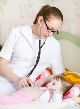 doctor examining girl with stethoscope photo