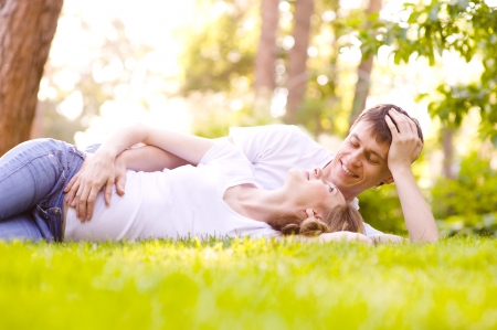 Happy Smiling Couple Relaxing on Green Grass Stock Photo
