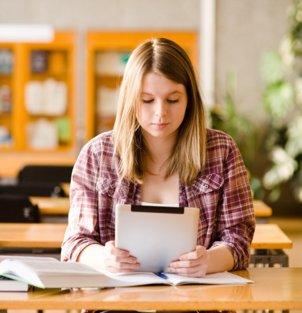 Teenage girl using electronic tablet at library photo