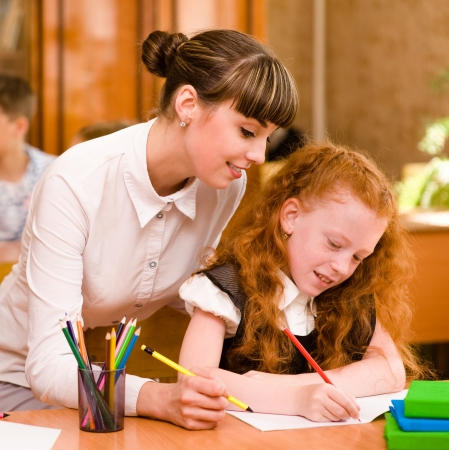 freckled: Teacher helps the student with schoolwork in school classroom Stock Photo