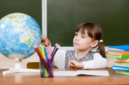 grade: Portrait of lovely girl considers Globe Stock Photo
