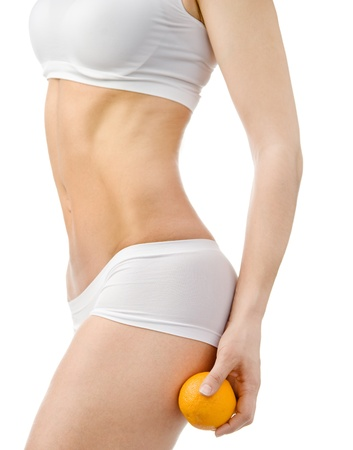 sexually: Slender female body holding orange on her leg on white background