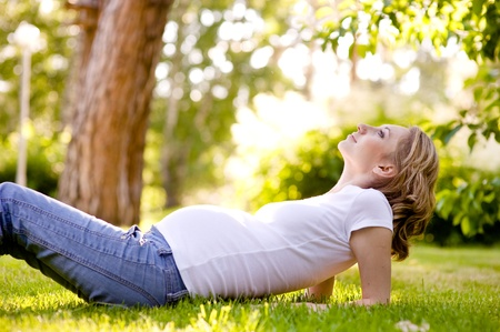 Beautiful pregnant woman lying on the grass in sunny day  looking up Stock Photo