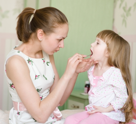 mother examining little girl s throat photo