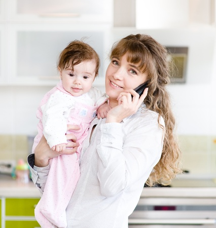 woman on the phone while holding her baby in her arms in the kitchen photo