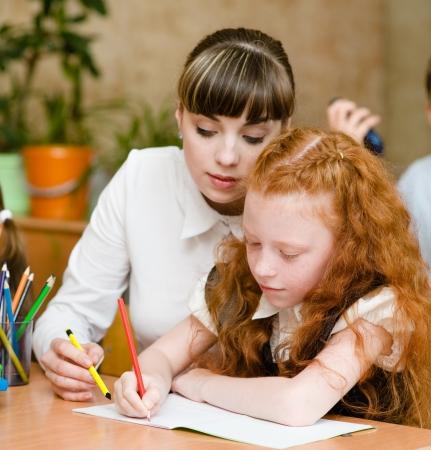 helps: Teacher helps the student with schoolwork in school classroom Stock Photo