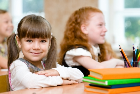 learner: Little girl sitting and studying at school class Stock Photo