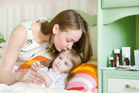 baby sick: mother kisses the sick child