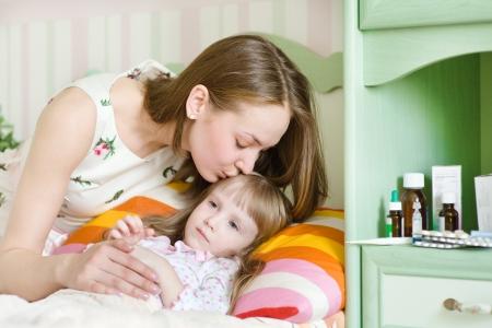 female kid: mother kisses the sick child