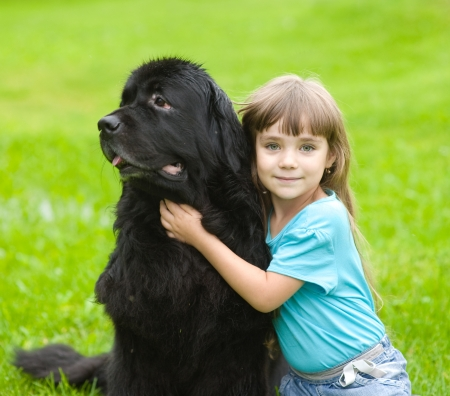 girl hugging Newfoundland dog photo