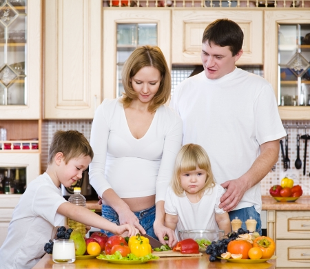 Family Preparing Salad In  Kitchen photo