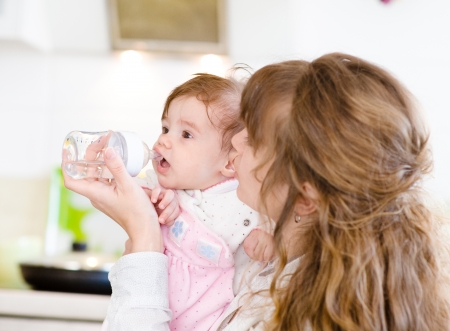 Mother feeding baby with feeding bottle in kitchen photo