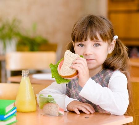 niños comiendo: colegiala retrato mirando a la cámara mientras almorzaba en Foto de archivo