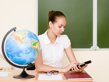 Teacher holding a tablet computer at classroom Stock Photo - 22379556